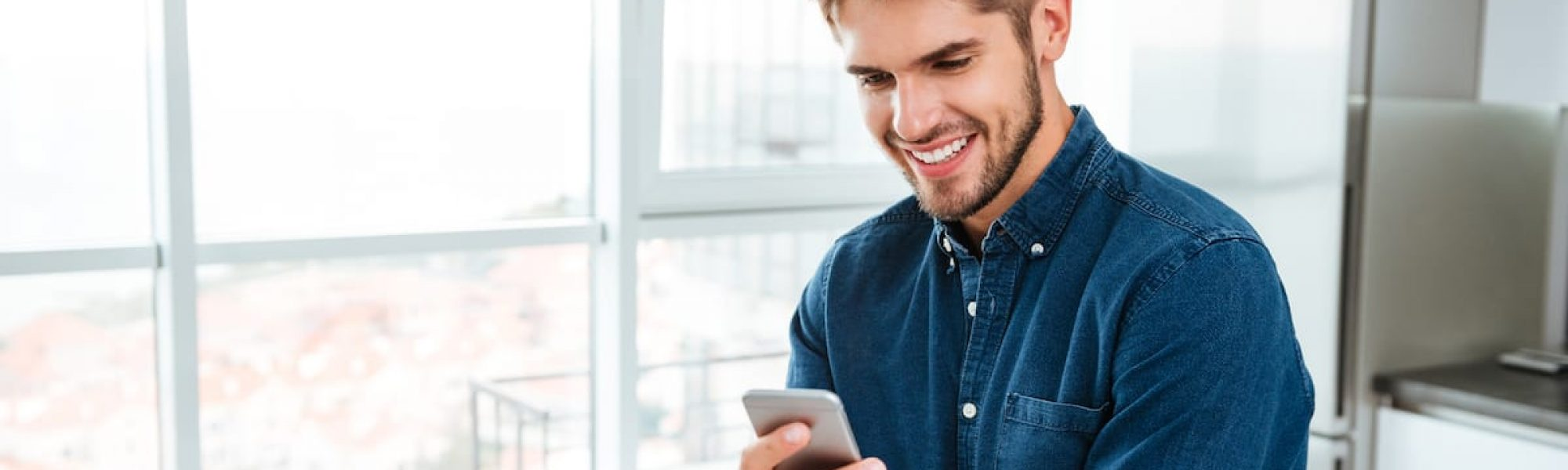 Picture of young man using a smartphone and smiling. Looking at smartphone.